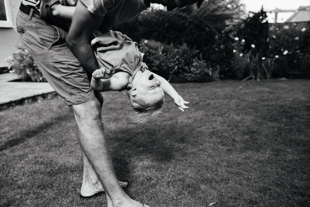 Black and white photograph of a daughter playing with her father