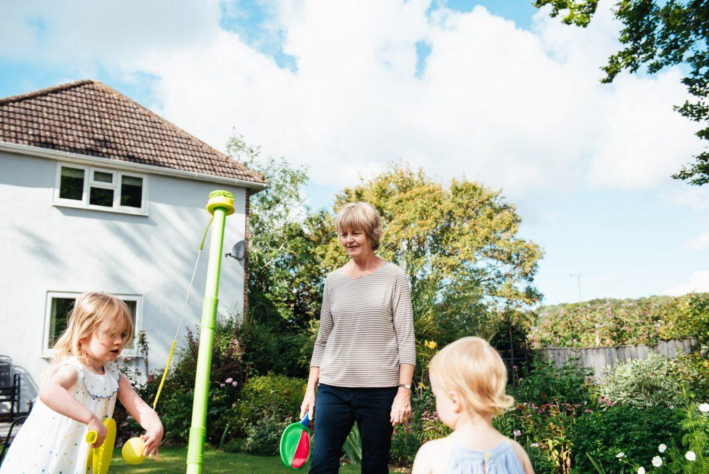 Grandmother plays with grandchildren in the garden