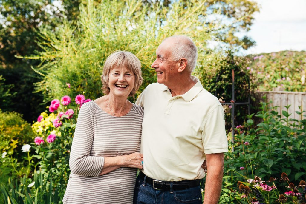 Grandparents smile and laugh together in outdoor family photoshoot