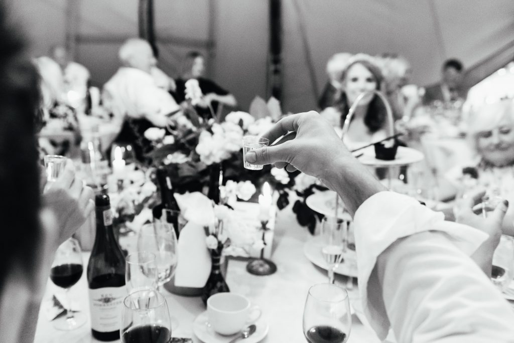 Guests raise a shot glass of vodka during speeches, Surrey wedding photography