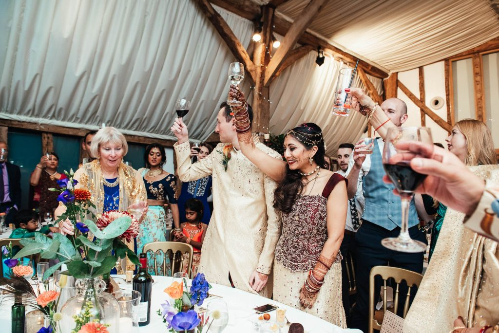 Wedding couple raise a glass during speeches