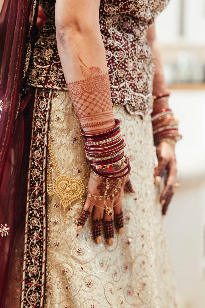 Wedding day details, brides hands decorated with henna and jewellery