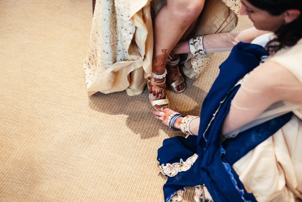 Bride is helped into her shoes, South Farm wedding day preparation photography
