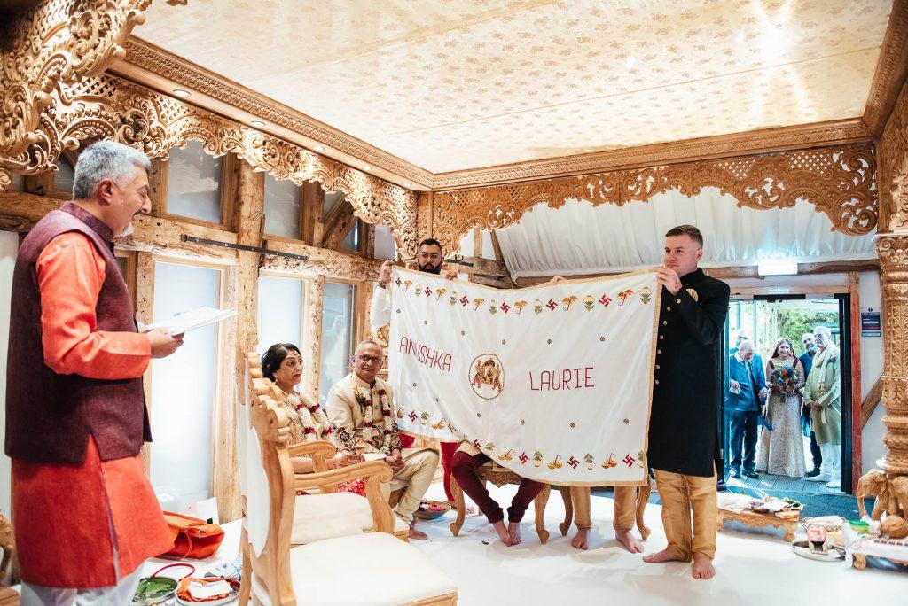 Groomsmen hide the groom from seeing his bride, South Farm wedding