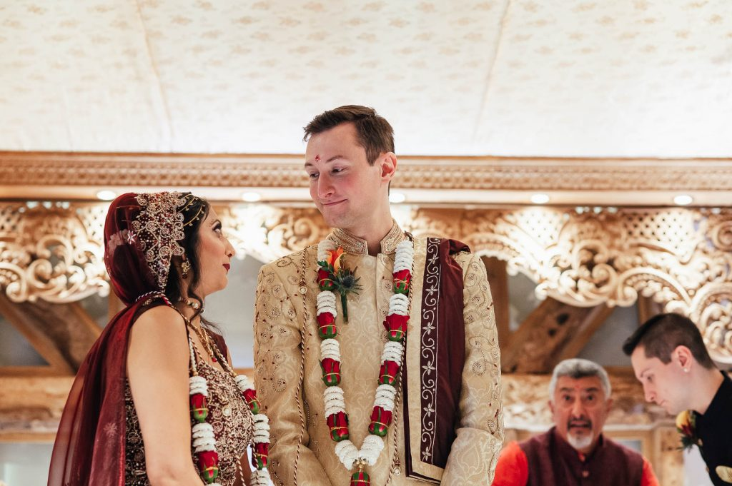 Groom smiles at his bride during their wedding ceremony