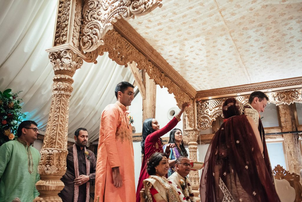 Family members throw flower petals over the couple during Hindu wedding ceremony