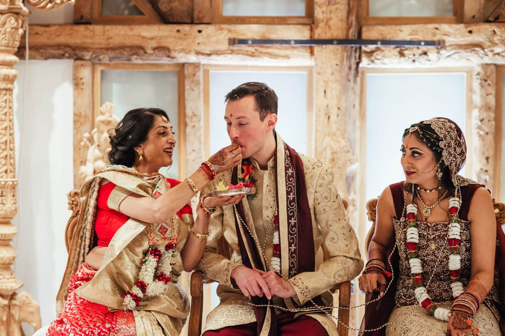 Mother of the bride feeds the groom during Hindu wedding rituals