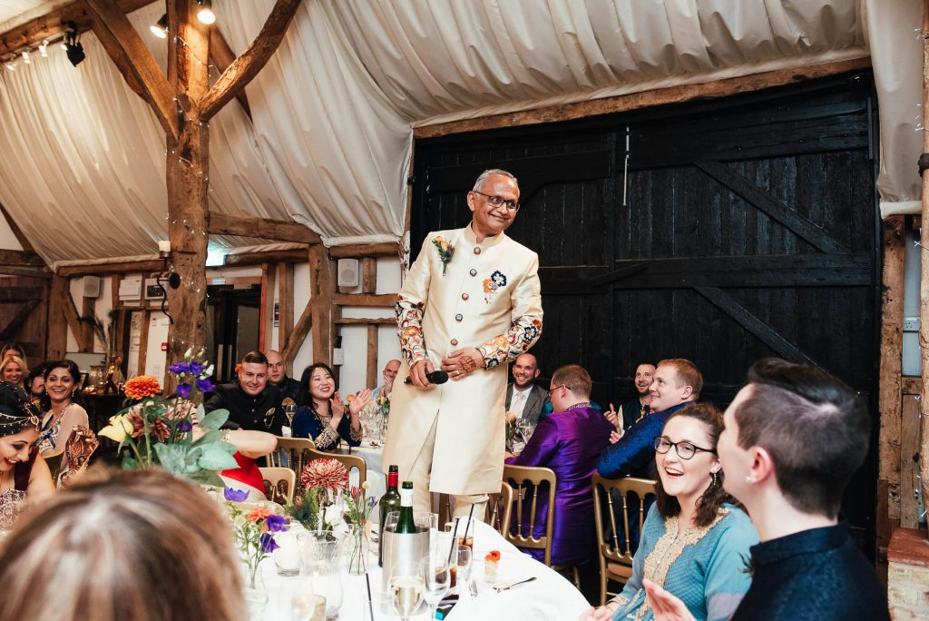 Father of the bride stands on chair to start his speech