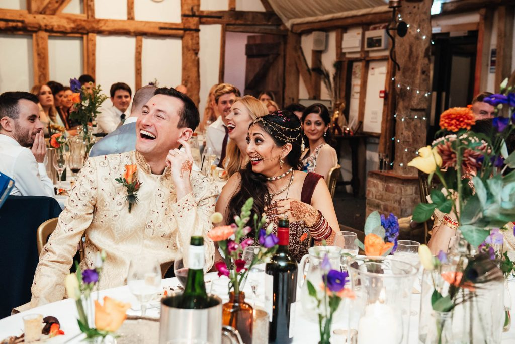 Bride and groom laugh during speeches, South Farm wedding