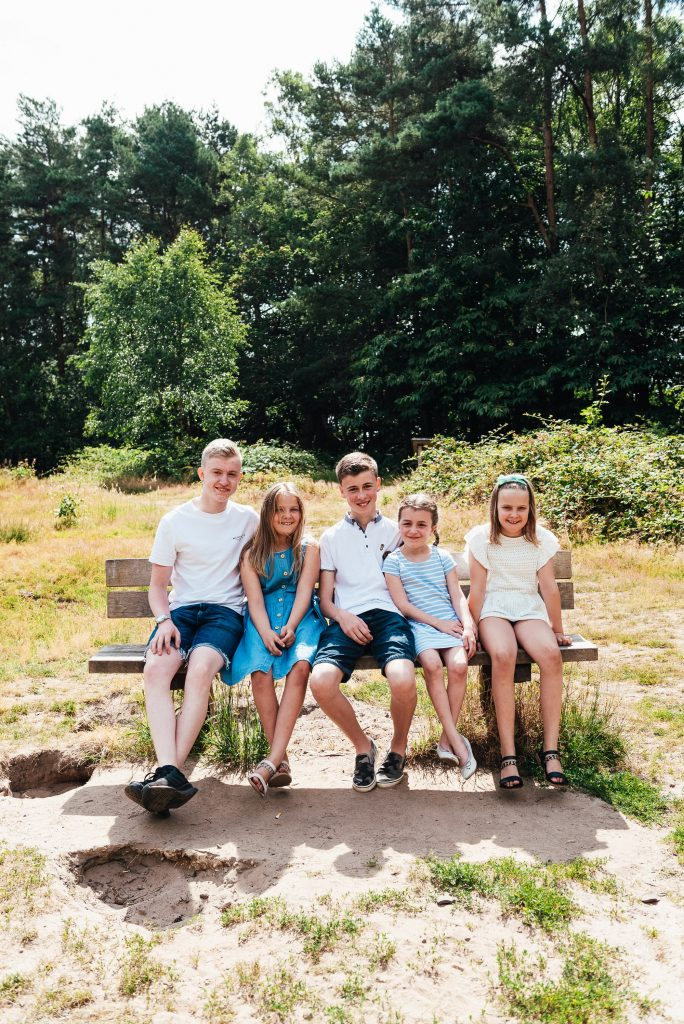 Cousins sit together for family portrait at Chantry wood family shoot