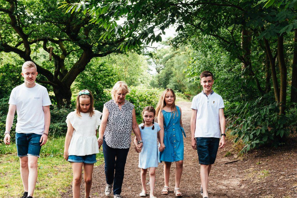 Grandmother walks with her grandchildren during Surrey woodland family shoot
