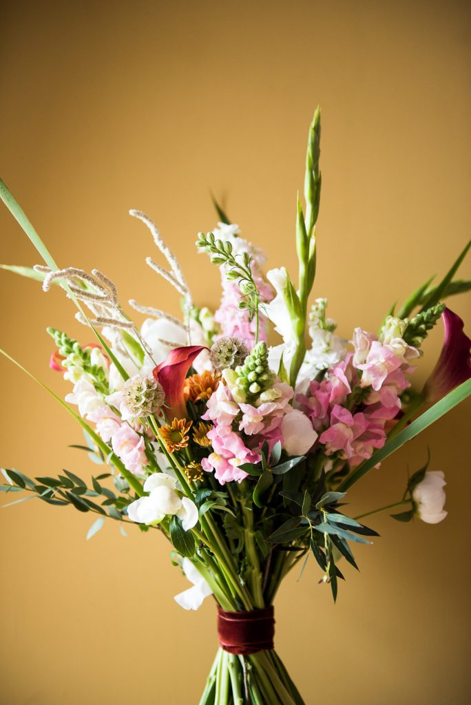 Wedding flower bouquet on mustard orange background