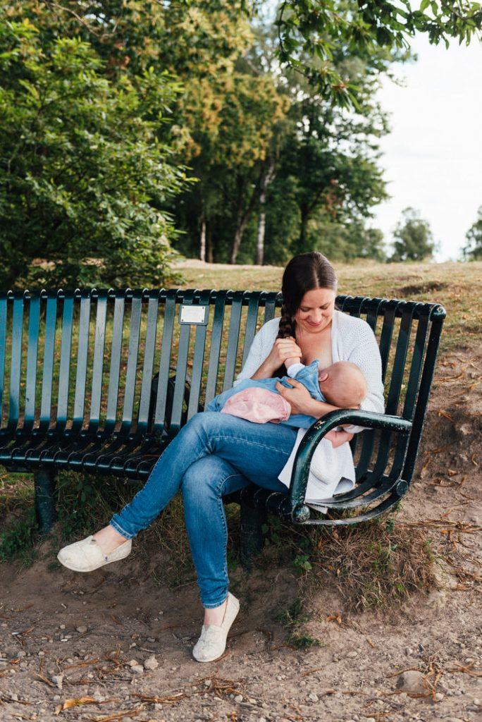 Mother breastfeeding baby outdoors, outdoor newborn photography