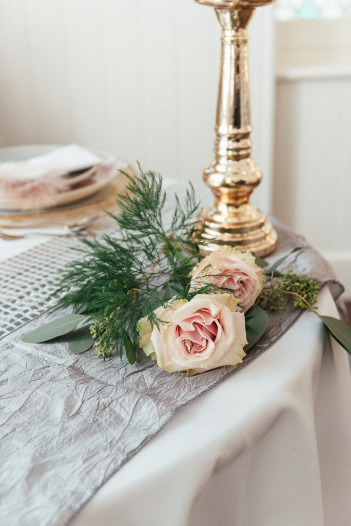 Rose florals and asparagus fern foliage table decor