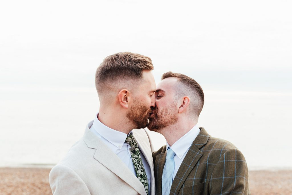 Grooms kiss passionately on Brighton Beach, lgbtq friendly wedding photographer
