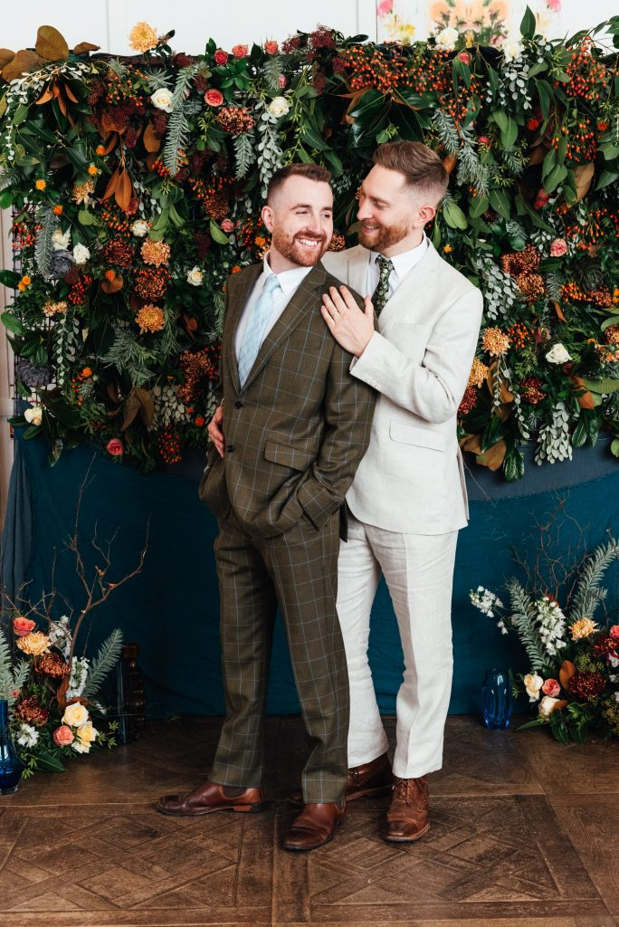 Grooms smile together in front of a flower wall backdrop