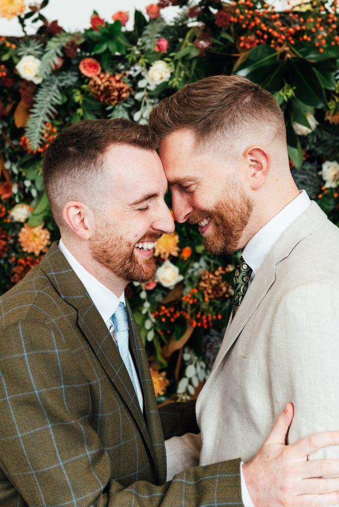LGBT friendly wedding photographer, grooms embrace lovingly