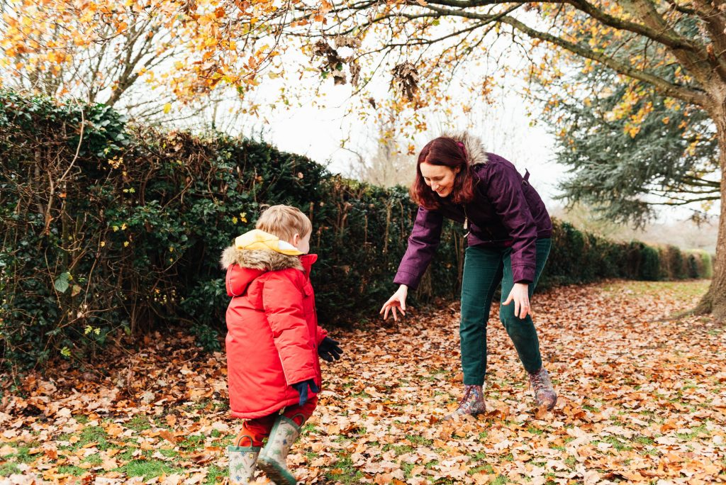 Fun and Candid Family Moment Playing In leaves