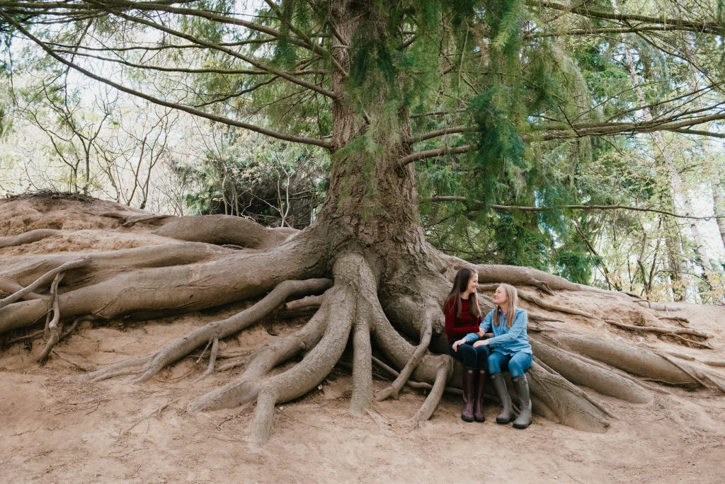 Couple Sit Together on Huge Tree Root System For Winkworth Arboretum Couples Shoot