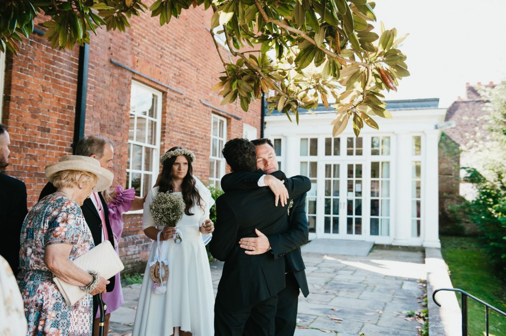 Groom embraces son after wedding ceremony